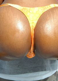 Cute ebony babe gets down and dirty at the beach in these pix